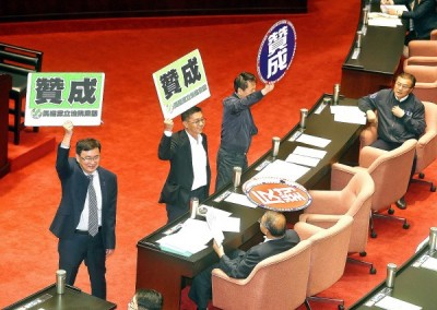 "Democratic Progressive Party legislators Huang Kuo-shu, left, Hsu Chih-chieh, second left, and Chinese Nationalist Party (KMT) Legislator Lin Wei-chou, second right, hold placards reading ""approve"" as an amendment to the Long-term Care Services Act passed its third reading at the legislature in Taipei yesterday. Photo: Fang Pin-chao, Taipei Times"