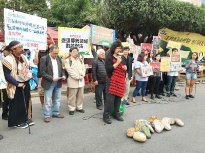 Aboriginal rights campaigners, including singer Nabu Husungan Istanda, left, singer/songwriter Kimbo Hu, fourth left, and documentary filmmaker Mayaw Biho, holding microphone, hold a news conference on Ketagalan Boulevard in Taipei yesterday as part of their ongoing protest against the government's definition of traditional Aborginal land and its committee for Aboriginal historic and transitional justice issues. Photo: CNA