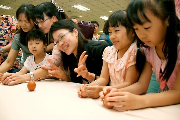 移民署舉辦端午節活動,除了有粽子品嚐外,新移民們還體驗傳統立蛋遊戲(記者姜翔翻攝)