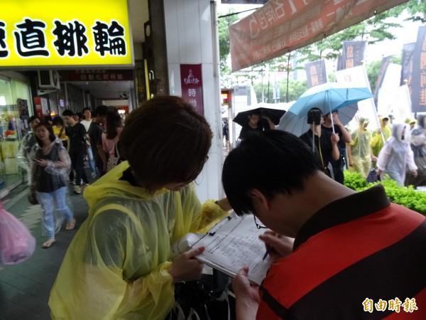 路邊民眾響應連署公投、罷免立委。(記者蘇芳禾攝)