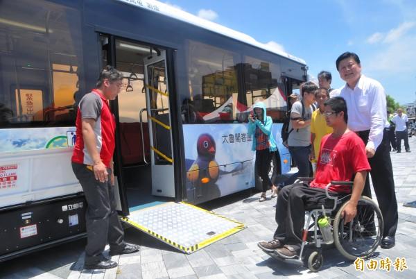 花蓮縣長傅崐萁推著身障人士,準備搭乘標榜低碳、低底盤的電動公車。(記者游太郎攝)
