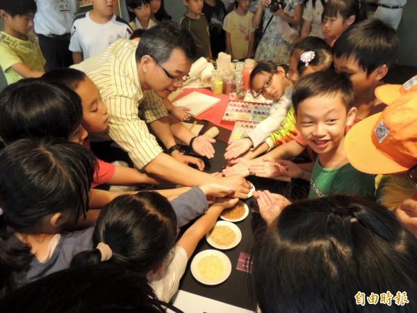 丹青風華-膠彩藝術特展,參觀學童爭相索取膠彩畫使用的「阿拉伯膠」品嚐。(記者歐素美攝)