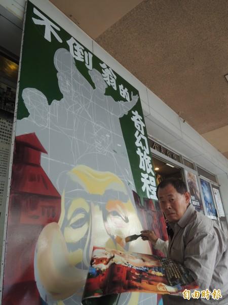 傳統手繪電影看板師傅顏振發,忙製「不倒翁的奇幻旅程」看板。(記者洪瑞琴攝)
