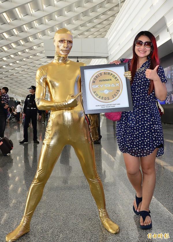 在桃園機場獲得有航空界金像獎Skytrax「2015全球及亞洲最佳機場服務人員」的兩項殊榮後,桃園機場金特別舉辦「小金人快閃活動」。(記者姚介修攝)