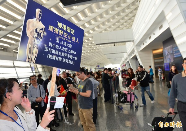 桃園機場金特別舉辦「小金人快閃活動」,出動「野生小金人」與遊客互動。(記者姚介修攝)