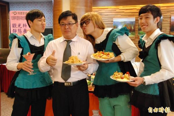 同德家商校長林元貴(左二)幫忙推薦食品科畢業班西點,被熱情的男僕打扮學生嚇了一跳。(記者陳鳳麗攝)