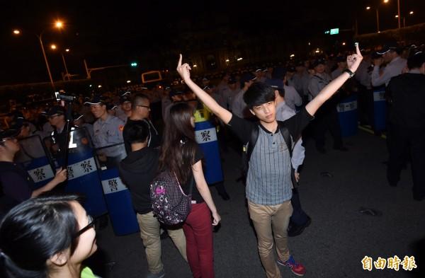 一名抗議成員在警方人牆前高舉中指。(記者羅沛德攝)