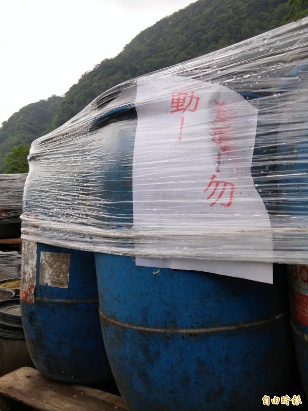 新竹縣尖石鄉武漢部落半個月前遭人堆放200多桶化學物質,現場貼有「有毒!勿動!」的警告標語。。(記者蔡孟尚攝)