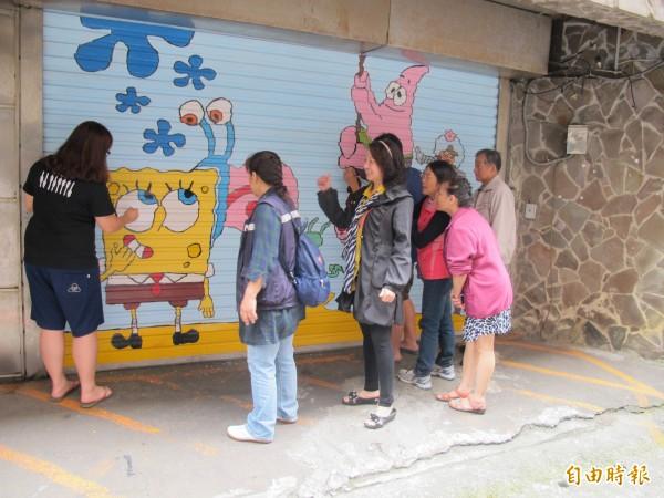 海大學生彩繪海綿寶寶等逗趣卡通人物,吸引居民駐足圍觀。(記者林欣漢攝)