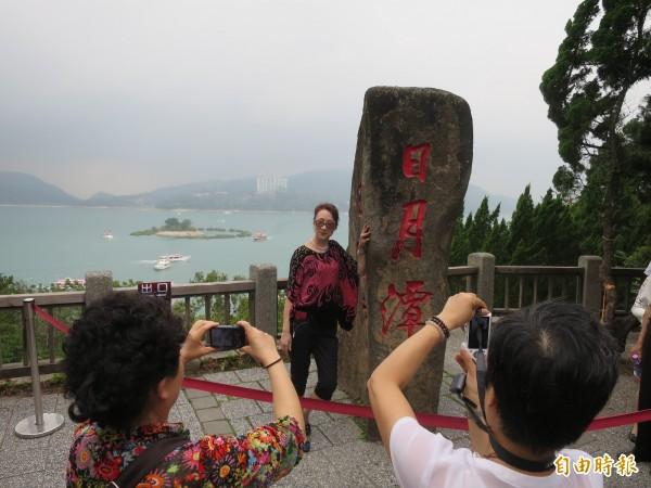 日月潭玄光寺地標石因可與拉魯島借位拍照,成為中客必遊景點。(記者劉濱銓攝)