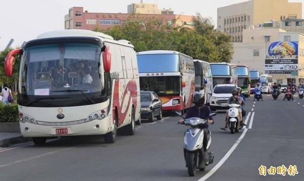 中國客遊覽車停在路邊,造成機車騎士騎上快車道。(記者葛祐豪攝)