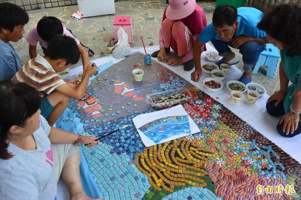 北門永隆社區正進行農村再生計畫,打造入口意象公園,社區居民拼貼馬賽克海洋意象,凝聚居民意識。(記者楊金城攝)