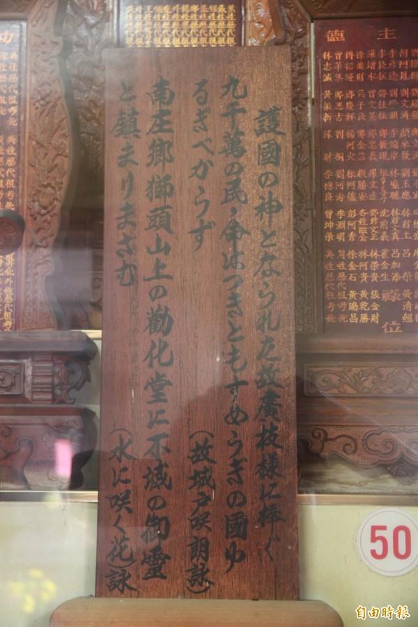 廣枝音右衛門夫婦牌位旁,放有記載安放始末的刻歌碑。(記者鄭鴻達攝)