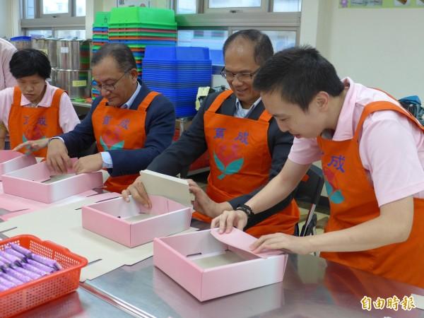 前行政院長游錫堃、立法委員高志鵬在憨兒的指導下,學習摺禮盒需要的紙盒。(記者李雅雯攝)