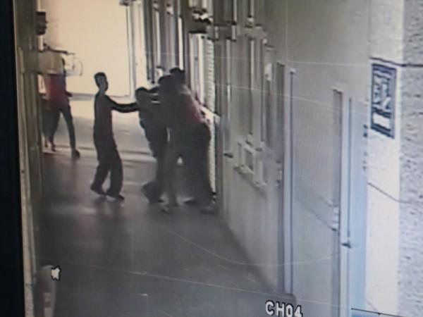 莊男(左一)伸手,從背後掐住校長脖子,校長一個踉蹌站不穩,其他老師趕快來解危。(記者王錦義翻攝監視器畫面)