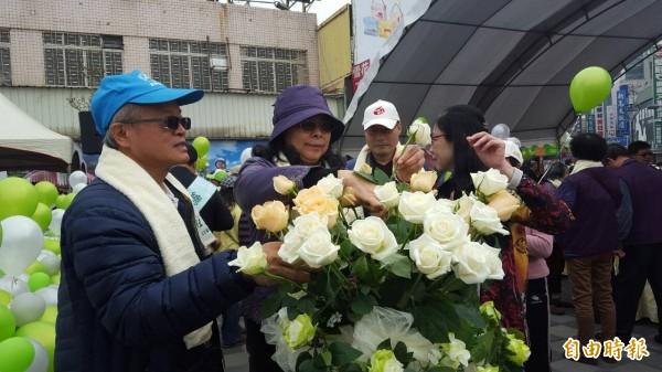 民眾手持玫瑰花向受難者獻花致敬。(記者丁偉杰攝)