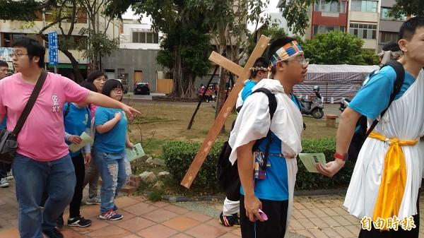 智青代表巧扮耶穌背負大十字架。(記者蔡文居攝)