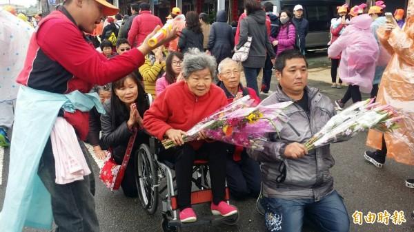 信眾坐輪椅或跪在路旁手持鮮花,虔誠等待白沙屯媽祖到來。(記者張勳騰攝)