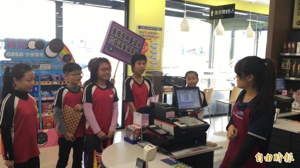 斗南僑真國小學童走上街頭,向店家宣導少用塑膠袋。(記者黃淑莉攝)