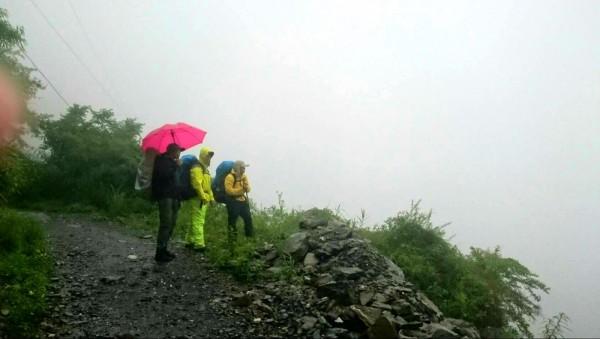 仁愛消防分隊搜救隊員在屯原登山口,因大雨和沿路坍方落石而受阻撤退,明日上午再出發。(仁愛消防分隊提供)