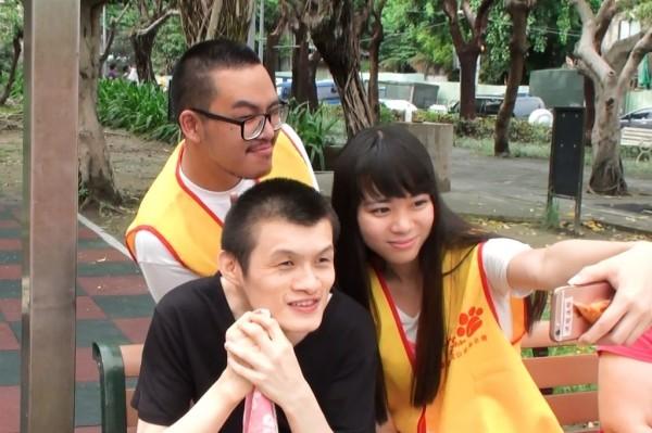 遠雄參訪鵬程啟能中心,並開心的與志工拍照。(贈物網提供)
