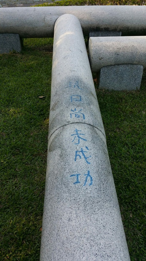 台中公園的鳥居,被人用藍漆噴寫「抗日尚未成功」。(記者張瑞楨翻攝)