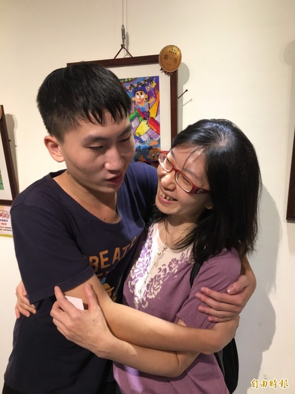 以「快樂出遊」作品連莊青少組第一名的王允中,感謝媽媽的不放棄,給了媽媽一個大擁抱。(記者楊綿傑攝)