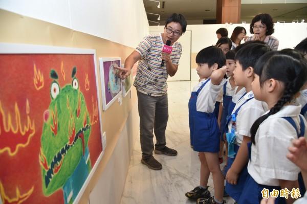 畫家以「孩子觀賞視角」為主,所有畫作都配合中低年級的兒童身高懸掛,家長不用把小孩抱高看畫,但要蹲下來陪孩子一起看畫。(記者張忠義攝)