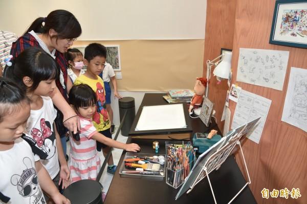 畫展另一個亮點是「畫家工作桌」,五位畫家都把自己工作桌上的物件真實搬到現場。(記者張忠義攝)