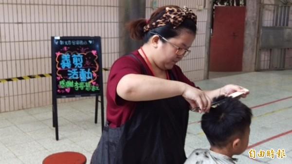 三峽區安溪國小志工李亭慧(紅衣者)發起義剪活動,為弱勢學童打理髮型,讓小朋友們開心不已。(記者張安蕎攝)