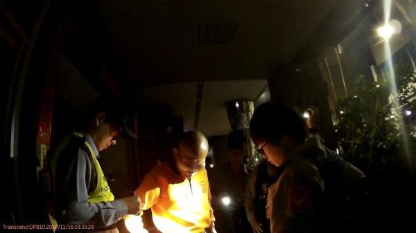 穿橘衣、藍鞋的許姓光頭男(中),半夜戴著墨鏡,涉嫌兩度在變電箱上燒紙箱、垃圾,遭警方依違反社秩法開罰6千元。(記者黃良傑翻攝)