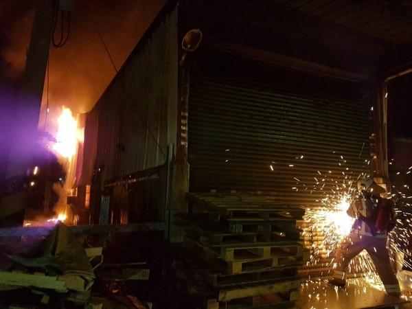 南市新營區鐵皮屋火災,消防員破壞鐵門救災。(記者王俊忠翻攝)