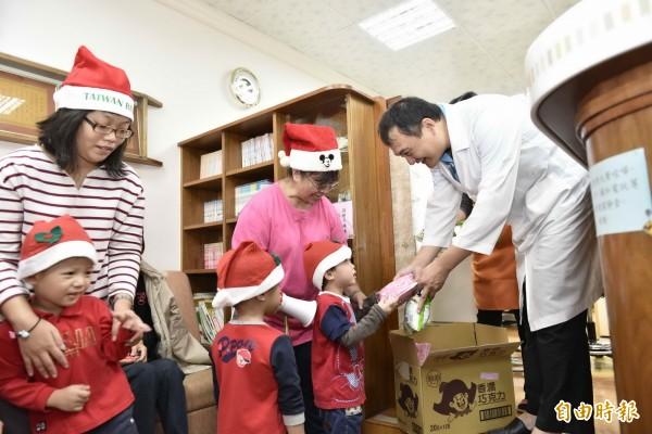 美善基金會小朋友,化身成小小耶誕老公公,到社區踩街祝福民眾平安喜樂。(記者蔡文居攝)
