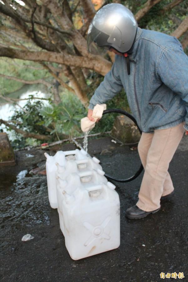 鄉親到三聖宮下提領山泉水回家使用。(記者黃美珠攝)