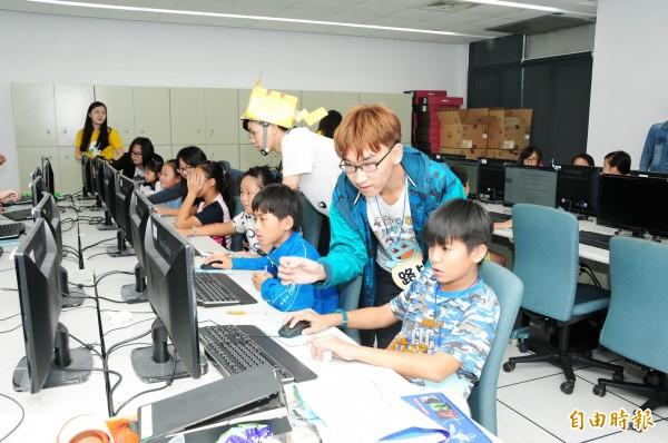 靜宜大學「小豆芽資訊志工團隊」指導學童學電腦。(記者張軒哲攝)