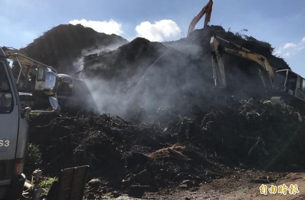 中壢堆置廢木材持續悶燒,附近空氣品質差。(記者李容萍攝)