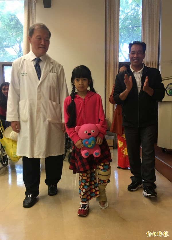 象腿女孩阮氏巒手術後左腿逐漸恢復,能正常行走了,手術醫師陳宏基和爸爸為她開心不已。(記者蔡淑媛攝)