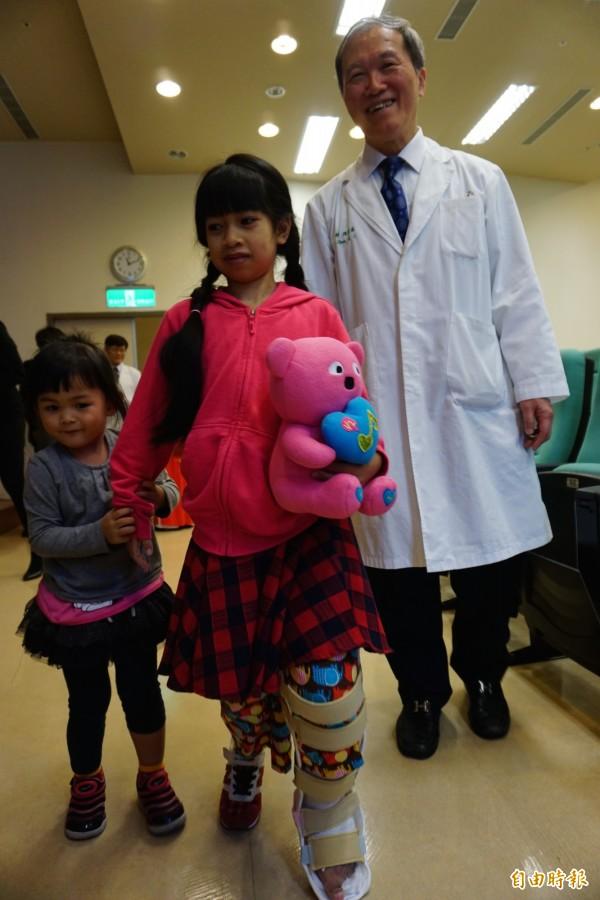象腿女孩阮氏巒手術後左腿逐漸恢復,能正常行走了,還能牽小妹妹一起走,手術醫師陳宏基為她開心不已。(記者蔡淑媛攝)