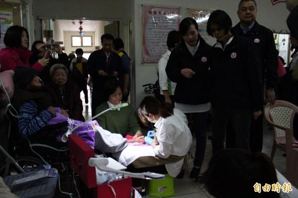 中華民國兒童及老人照護協會請來專業人員為老人家處理足部指甲。(記者林宜樟攝)