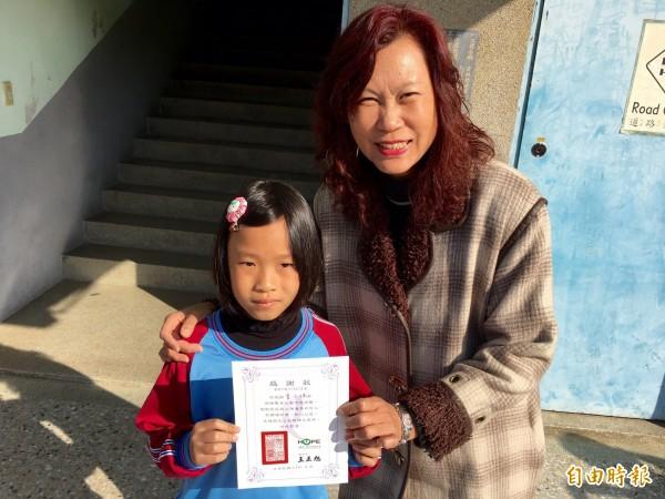 虎尾安慶國小校長李瑪莉頒發好人證書給捐髮的女學童曾子瑀。(記者廖淑玲攝)
