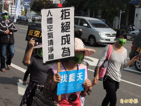民眾舉牌拒絕成為人體空氣清淨機。(記者王榮祥攝)