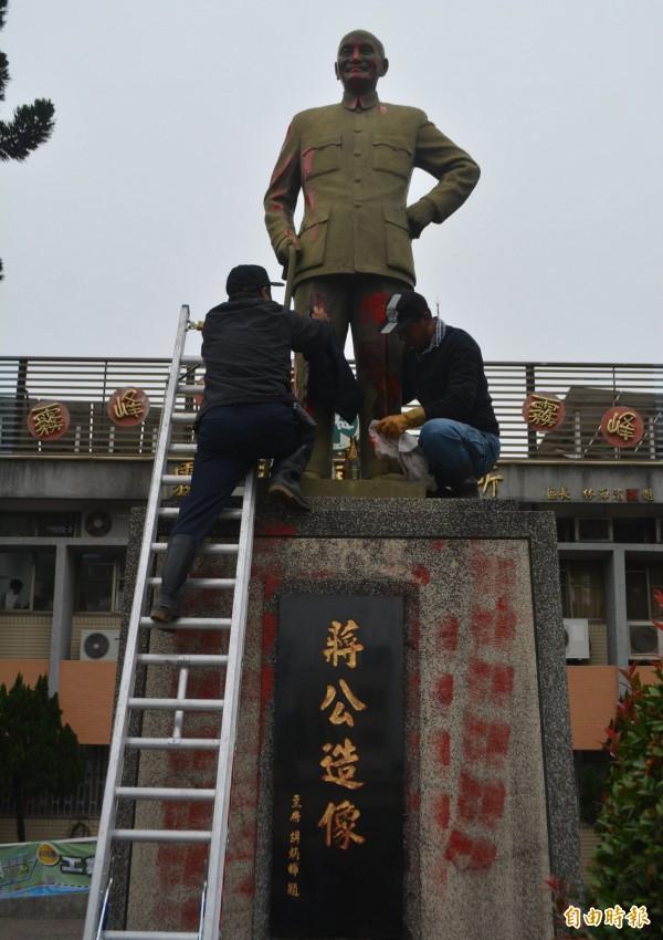 台中市霧峰區公所前的蔣介石銅像,今天凌晨遭人塗抹紅漆抗議,區公所上午趕緊派人爬上銅像把紅漆擦掉。(記者陳建志攝)