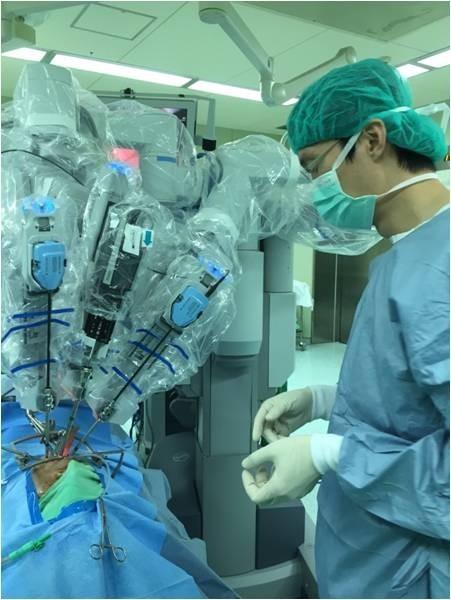 曾良鵬(右)使用達文西機械手術系統,為病患切除腫瘤。(記者洪定宏翻攝)