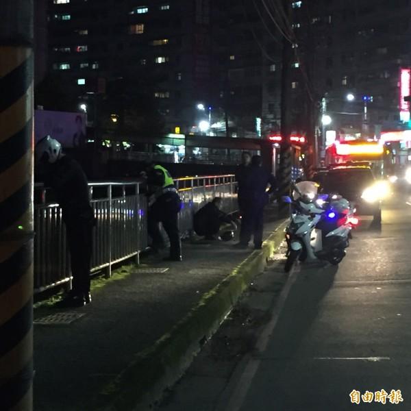 大武崙派出所的警員在溪邊,用手電筒監控毒品流向,易男則坐在一旁。(記者吳昇儒攝)