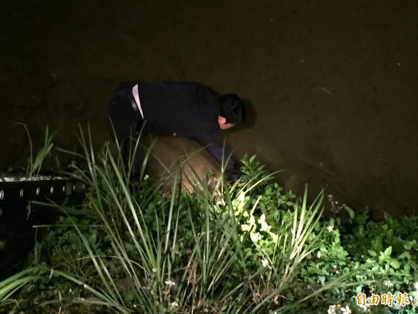 所長葉錦志在武崙溪中找到毒品。(記者吳昇儒攝)