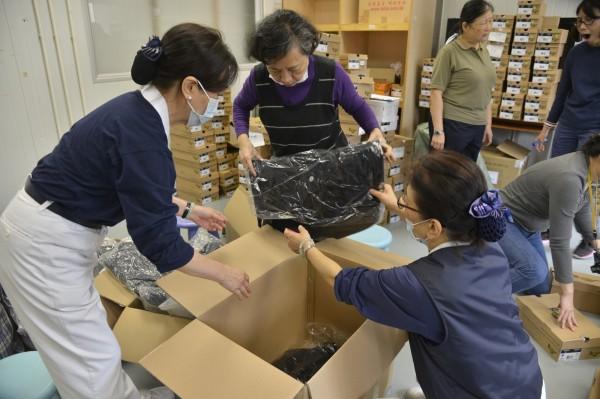 香港民眾捐贈的,除了鞋子外,也有一些衣服,志工也是整齊的重新裝箱。(慈濟基金會提供)