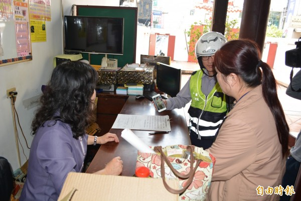 失蹤老翁今天出現在彰化市區,員警持老翁照片向民眾詢問行蹤。(記者湯世名攝)