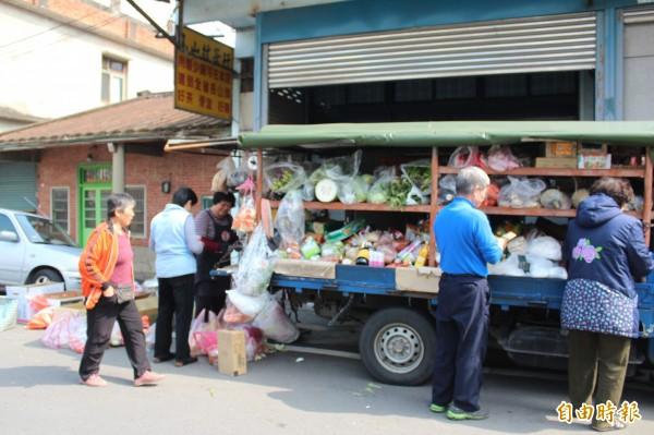 賣菜媽媽謝春枝(左3)在義民廟入口牌樓前賣菜36年,跟很多客戶情如朋友。(記者黃美珠攝)