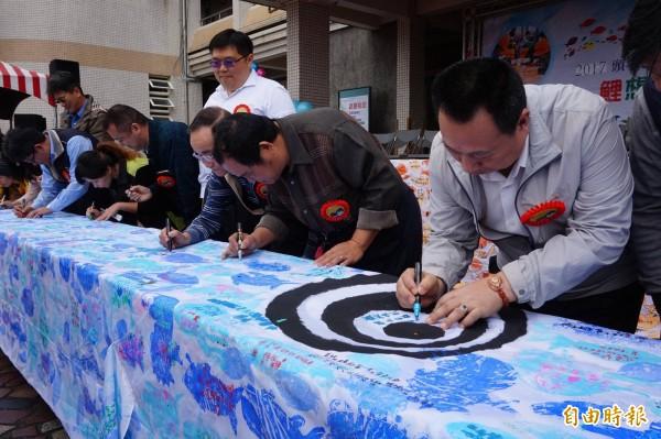 頭城鎮長曹乾舜(右)也在鯉魚旗上寫下祝福。(記者林敬倫攝)