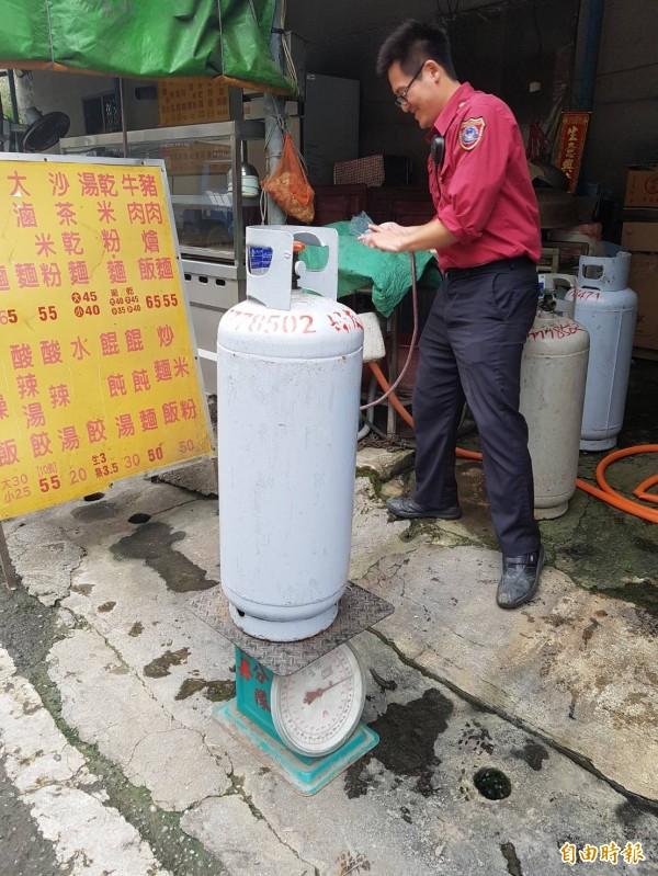 消防局稽查商家使用的桶裝瓦斯是否為逾期鋼瓶。(記者葉永騫攝)